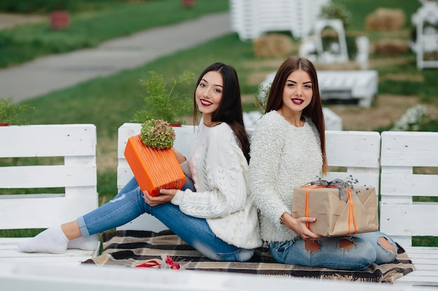 Two beautiful women sitting on a bench and holding in their hands gifts