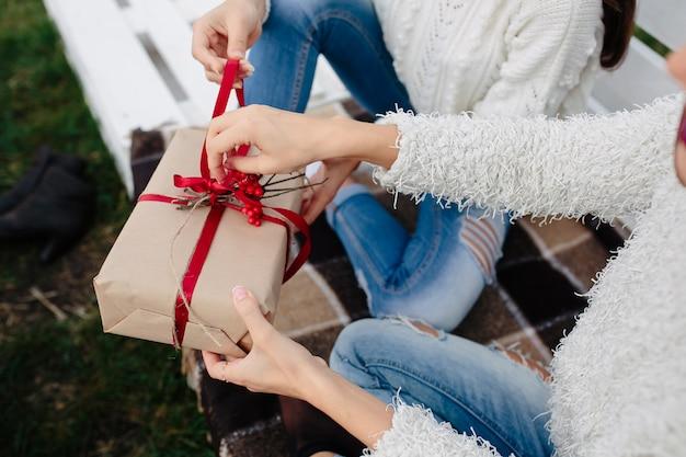 Две красивые женщины сидят на скамейке и держат в руках подарки, крупным планом