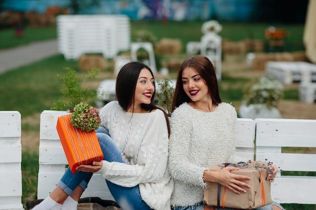 Две красивые женщины сидят на скамейке и держат в руках подарки