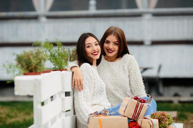 Две красивые женщины сидят на скамейке, держат в руках подарки и смотрят