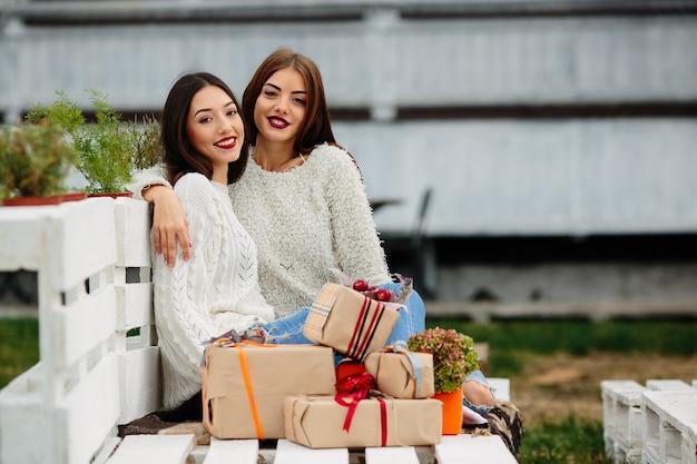 ベンチに座って、手に贈り物を持って、探している2人の美しい女性