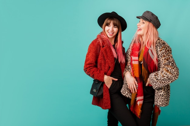 Due belle donne in eleganti cappotti di pelliccia sintetica e sciarpa di lana in posa sulla parete turchese