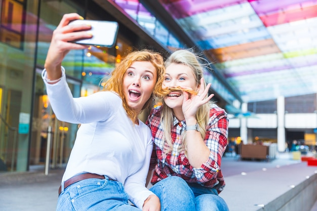 Two beautiful women taking a funny selfie