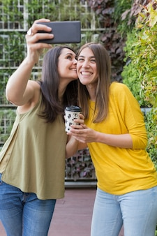 Two beautiful women taking a selfie with mobile phone. one is holding a cup of coffee and kissing her friend. they are laughing. outdoors lifestyle and friendship concept