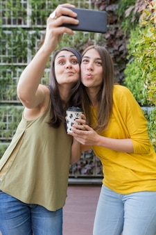 Two beautiful women taking a selfie with mobile phone. one is holding a cup of coffee. they are laughing. outdoors lifestyle and friendship concept