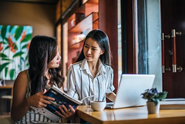 Две красивые женщины говорят все вместе в кафе кафе