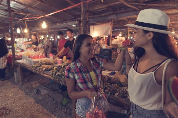 Two beautiful women tasting watermelon on traditional street market in asia