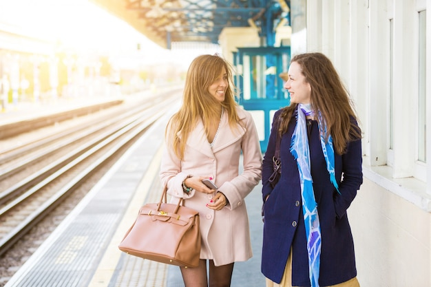 Two beautiful women walking along platform at train station
