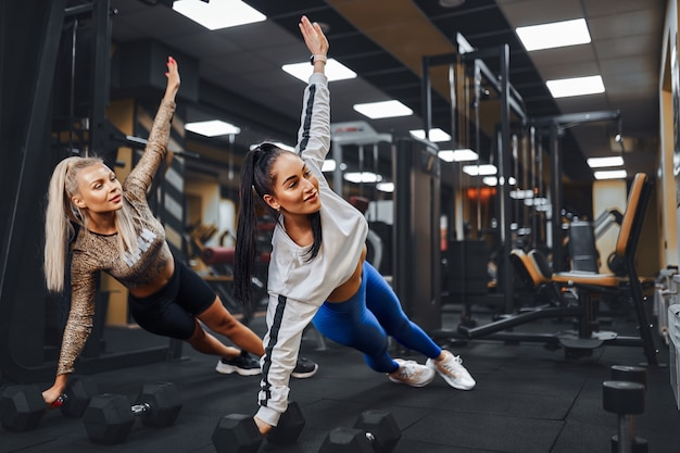 Two beautiful women with athletic figures perform a side plank pose in gym