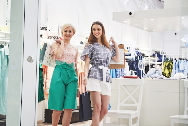 Two beautiful women with bags looking at each other with smile while walking at the clothing store