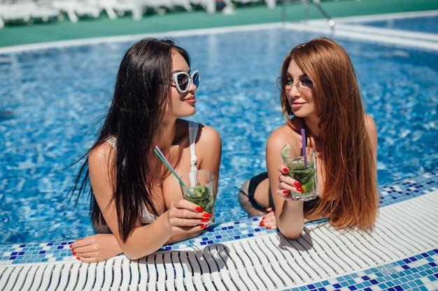 Две красивые женщины с красивыми фигурами в бело-черном купальнике загорают у бассейна и пьют освежающие коктейли.