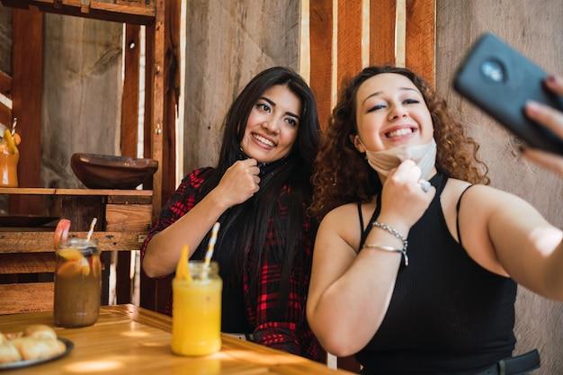 バーに座っているオープンマスクの2人の美しい女性が自分撮りをします。