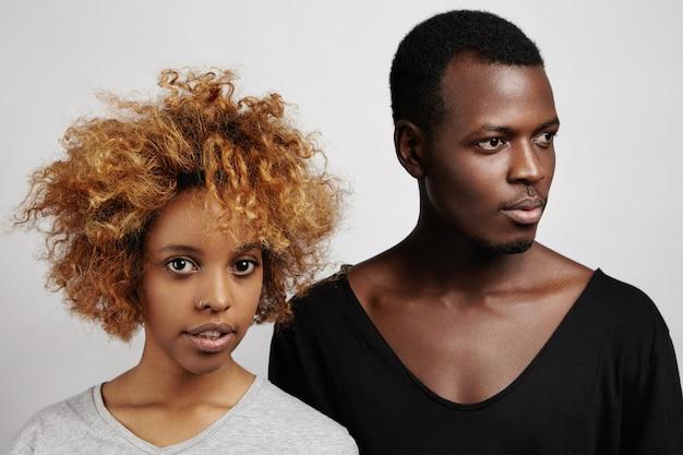 Два красивых молодых африканских человека, стоя у белой стены.