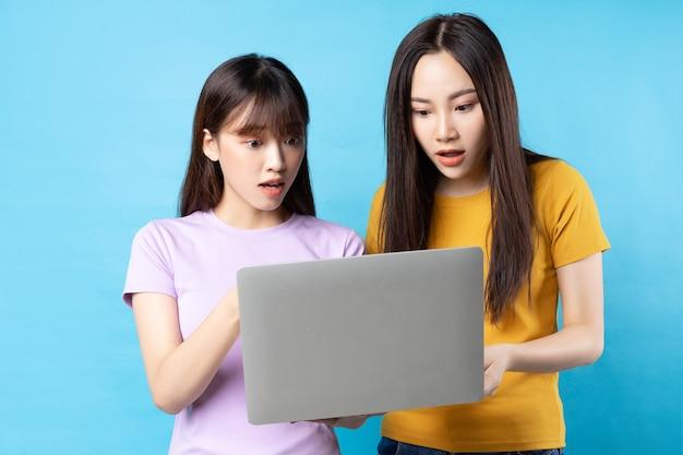 青い壁にラップトップを使用して2人の美しい若いアジアの女の子