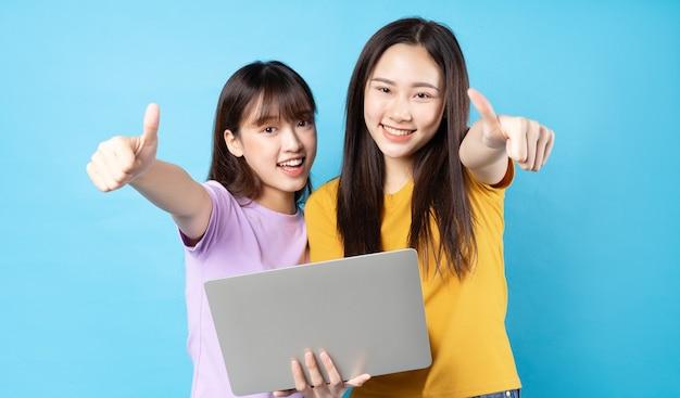 Две красивые молодые азиатские девушки, использующие ноутбук на синей стене