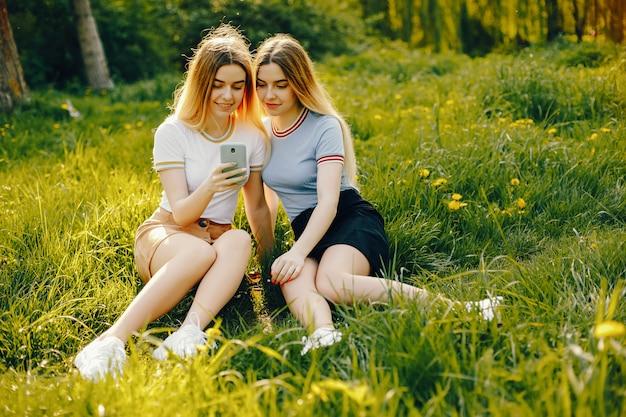 光沢のあるブロンドの髪とスカートと電話で座っている2人の美しい若い美しい女の子