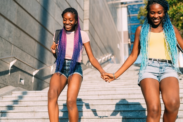 Two beautiful young black sisters walking downstairs together holding hands