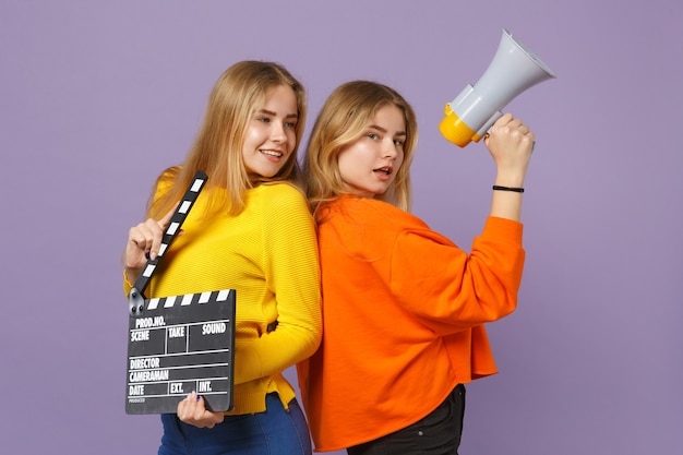 Две красивые молодые блондинки сестры-близнецы держат классический черный фильм, делая с 'хлопушкой', кричат на мегафон, изолированный на фиолетово-синей стене. концепция семейного образа жизни людей. .