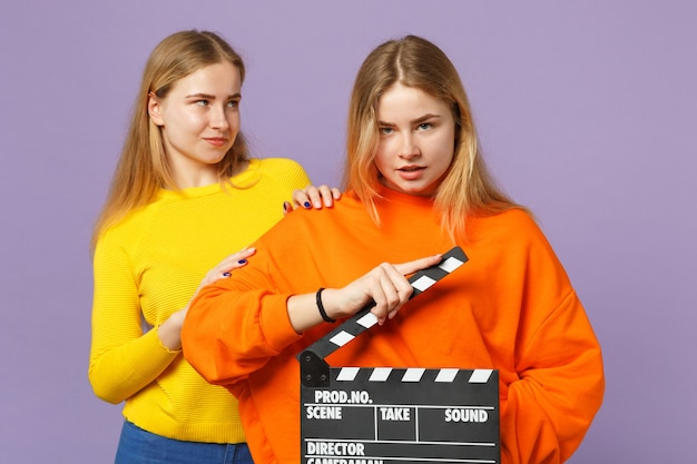 화려한 옷을 입고 두 아름 다운 젊은 금발 쌍둥이 자매 소녀 보라색 파란색 벽에 절연 clapperboard 만들기 클래식 블랙 영화를 개최합니다. 사람들이 가족 라이프 스타일 개념.