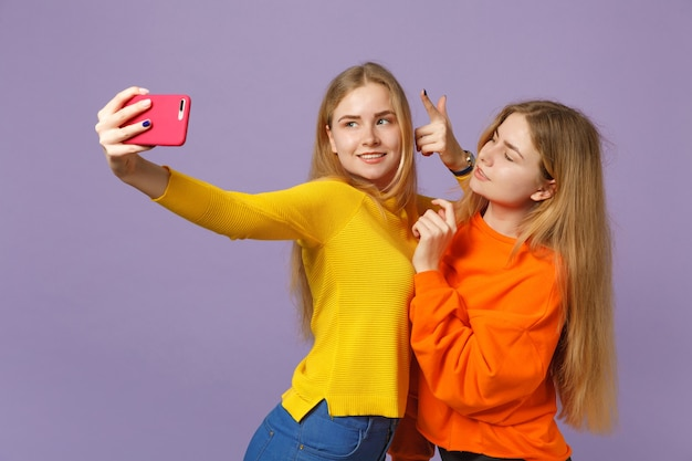 パステルバイオレットブルーの壁に隔離された携帯電話でselfieショットをしている鮮やかな服を着た2人の美しい若いブロンドの双子の姉妹の女の子。人々の家族のライフスタイルの概念。