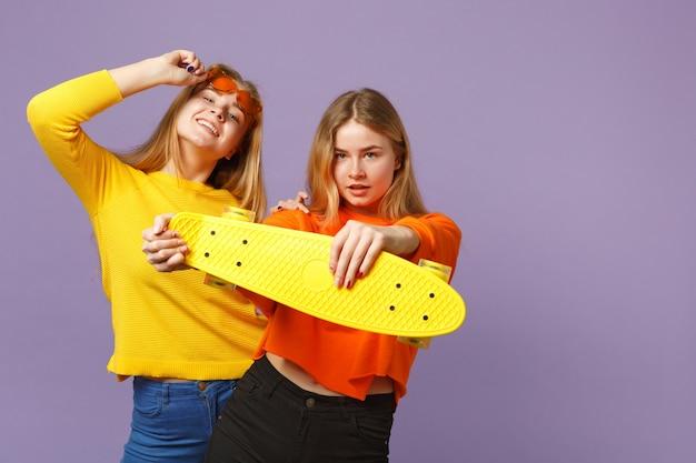 鮮やかな服を着た2人の美しい若い金髪の双子の姉妹の女の子、ハートの眼鏡はパステルバイオレットブルーの壁に分離された黄色のスケートボードを保持します。人々の家族のライフスタイルの概念。