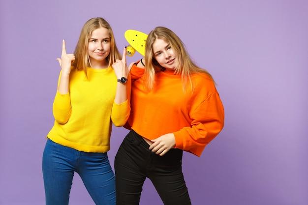 人差し指を上に向けて鮮やかな服を着た2人の美しい若いブロンドの双子の姉妹の女の子は、紫の青い壁に分離された黄色のスケートボードを保持します。人々の家族のライフスタイルの概念。