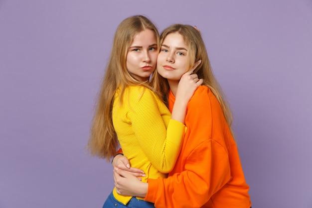 두 아름 다운 젊은 금발 쌍둥이 자매 소녀 포옹 하 고 파스텔 바이올렛 파란색 벽에 고립 된 생생한 화려한 옷에. 사람들이 가족 라이프 스타일 개념.
