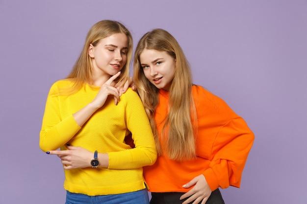 두 아름 다운 젊은 금발 쌍둥이 자매 소녀 서, 파스텔 바이올렛 파란색 벽에 고립 된 생생한 화려한 옷을 입고. 사람들이 가족 라이프 스타일 개념.