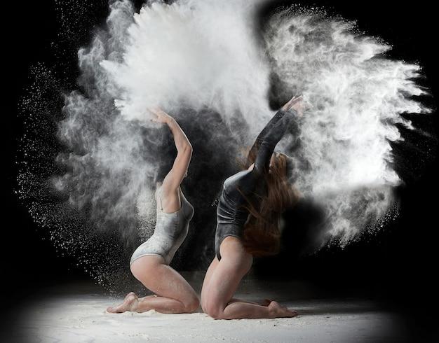 스포츠 그림과 검은 바디 수트에 두 아름 다운 젊은 백인 여성이 춤을