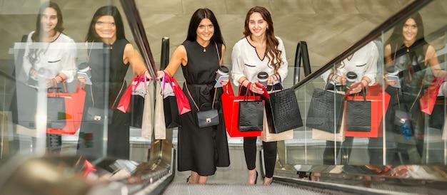 ショッピングモールでカメラを見ているエスカレーターで上に移動する買い物袋を持つ2人の美しい若い白人女性