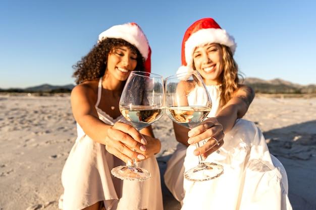 サンタクロースの帽子をかぶってカメラを見ている白ワイングラスで乾杯する2人の美しい若い女性