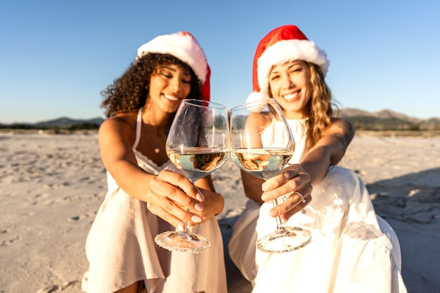 Two beautiful young female toasting with white wine glasses looking at camera wearing santa claus hat