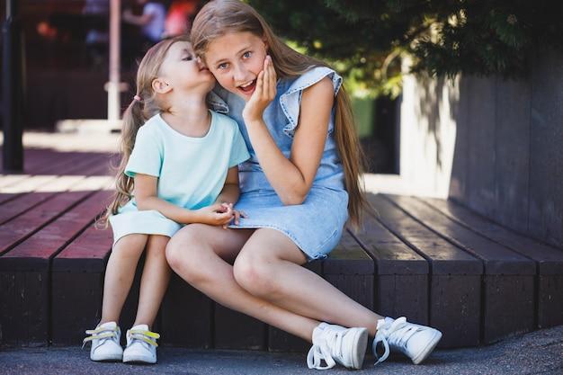 두 명의 아름다운 어린 소녀가 베란다에 앉아 비밀입니다.