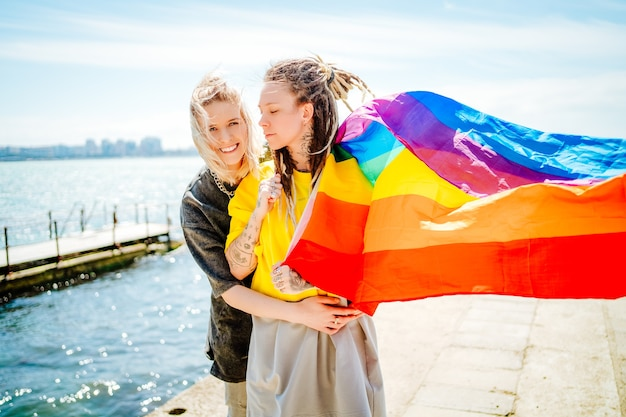 Two beautiful young girls cuddle on the beach with a rainbow flag.