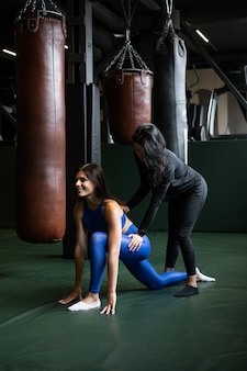 ジムでフィットネスをしている2つの美しい若い女の子。背中と脚の筋肉を伸ばします。