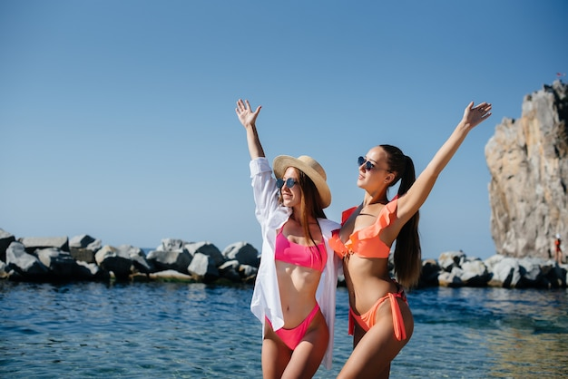 Two beautiful young girls in glasses and bikinis are standing and enjoying themselves on the ocean shore against the background of huge rocks on a sunny day. tourism and tourist trips.