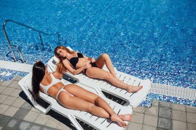Две красивые молодые девушки с красивыми фигурами загорают у бассейна и разговаривают