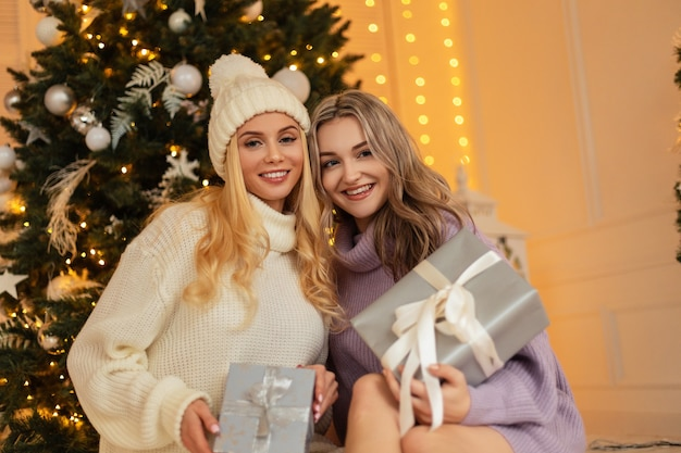 ヴィンテージのニットセーターと自宅のクリスマスツリーの近くに座っている贈り物とファッショナブルな帽子の笑顔で2人の美しい若い幸せな女性