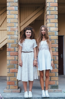 Two beautiful and young hipster style blonde women posing together on the street. white vintage dresses
