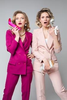Две красивые молодые дамы в стильных костюмах позируют на сером фоне и удивленно смотрят в камеру. концепция моды