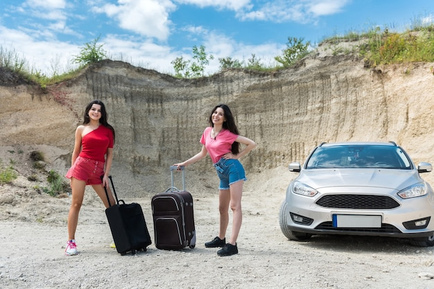 Two beautiful young people enjoy summer time adventure on car