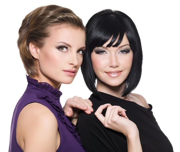 흰색 배경 위에 함께 서있는 두 아름 다운 젊은 관능적 인 매력적인 여자