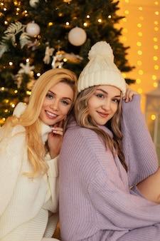ニットのファッショナブルなセーターと帽子をかぶった2人の美しい若い姉妹の女の子がクリスマスツリーの近くに座っています。冬休み