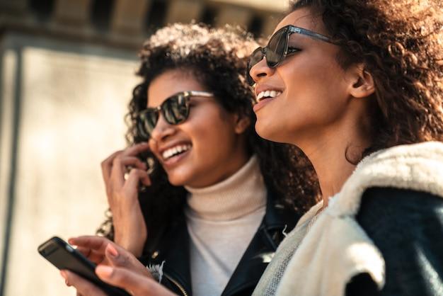 Две красивые молодые стильные африканские женщины вместе гуляют по улице, разговаривают по мобильному телефону