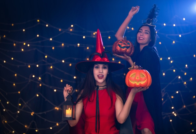 Two beautiful young surprised woman in halloween party.