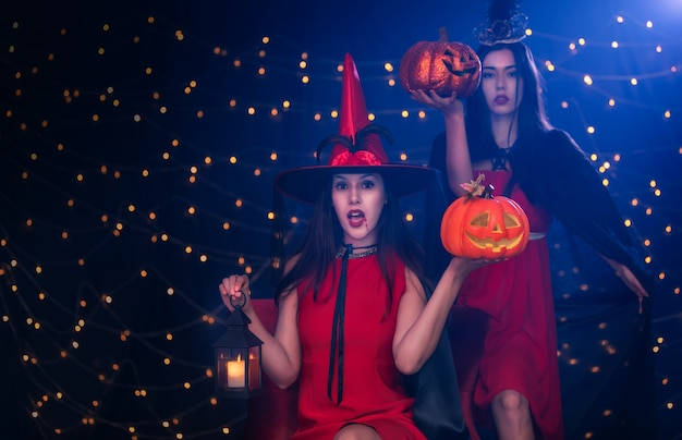 Two beautiful young surprised woman in witches holding and acting scary at halloween party