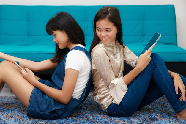 Two beautiful young teenager asian girls lay on each back and using mobile devices, smartphone and tablet connet to internet