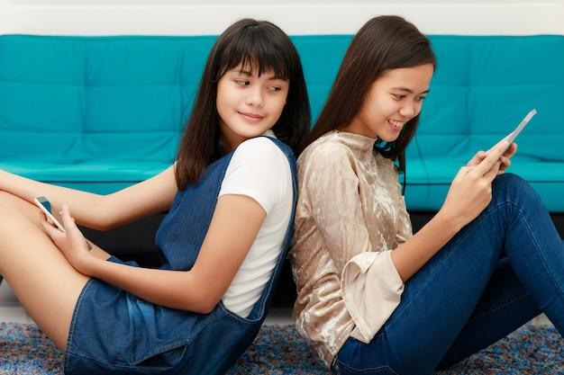두 명의 아름다운 10대 아시아 소녀들이 등을 대고 누워 모바일 기기, 스마트폰, 태블릿 인터넷을 사용합니다.