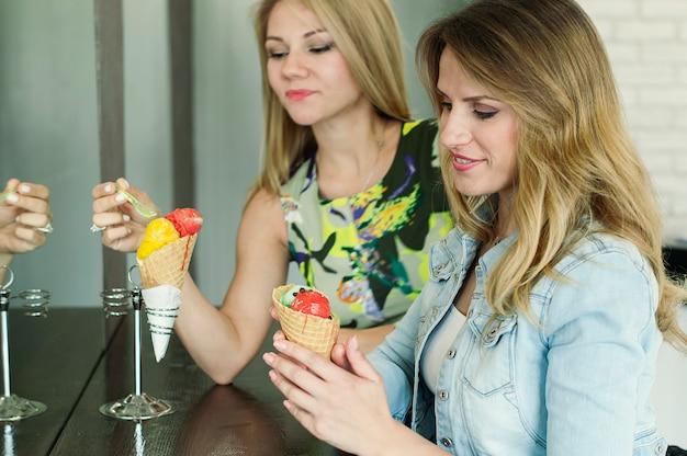 Две красивые молодые женщины едят итальянское мороженое