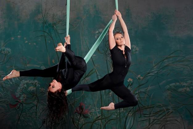 Две красивые молодые женщины в обтягивающем черном спортивном костюме занимаются йогой на подвесе